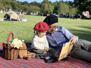 芝生のある公園ピクニックで読書をするパパと娘の写真・画像素材[1600981]