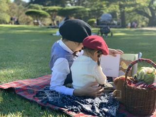 公園で本を読むパパと娘の後ろ姿の写真・画像素材[1600995]