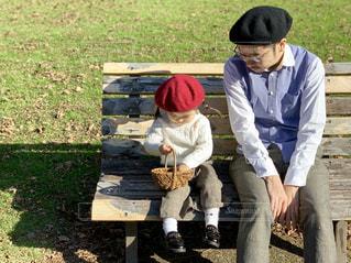 秋コーデでベンチに座っているパパと娘の写真・画像素材[1600998]