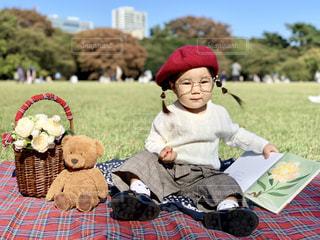 ピクニック中絵本に飽きた女の子とくまのぬいぐるみの写真・画像素材[1601044]