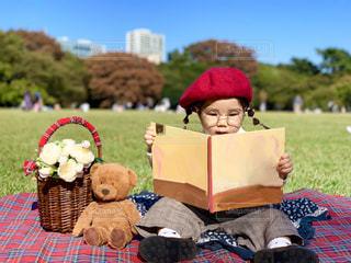 公園でくまのぬいぐるみと仲良く絵本を読む女の子の写真・画像素材[1601064]