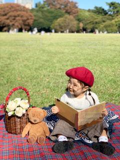 くまのぬいぐるみに絵本を読んでいる女の子の写真・画像素材[1601069]