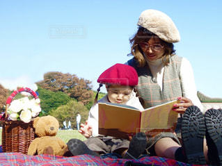 公園で絵本の読み聞かせをするママと娘の写真・画像素材[1601097]