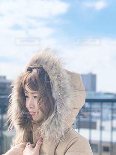 空の下フードを被ったふわふわファーの女性の写真・画像素材[1614005]