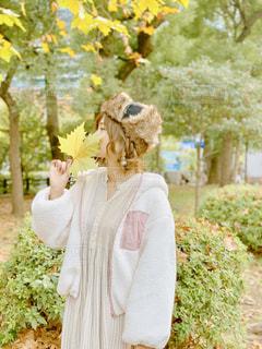 大きなもみじの葉っぱで顔を隠す女性の写真・画像素材[1653615]