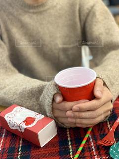 クリスマスデート中カップで暖まる男性の手元の写真・画像素材[1654984]