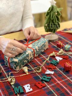 クリスマスパーティーのプレゼントを開ける女性の手元の写真・画像素材[1655000]
