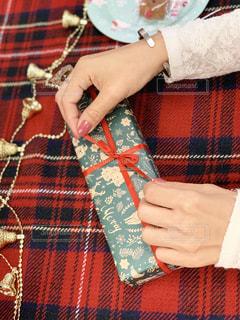プレゼントのラッピングをする女性の手元の写真・画像素材[1655001]
