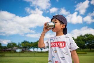 夏空の下で美味しそうにジュースを飲む少年の写真・画像素材[2125813]