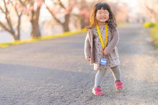 桜の咲く歩道を歩いている小さな女の子の写真・画像素材[2329188]