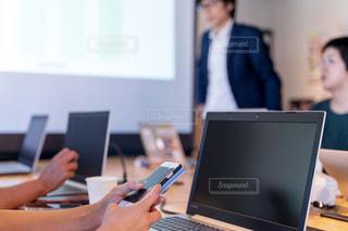 ラップトップコンピュータを使ってテーブルに座っている人々のグループの写真・画像素材[2405098]