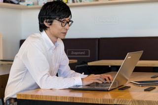 ノートパソコンを見て机に座っている人の写真・画像素材[2415305]