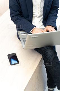 ラップトップとスマホを操るビジネスマンの写真・画像素材[2893661]