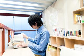 ノートパソコンと本で作業する男性の写真・画像素材[2893963]