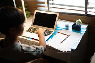 子ども,1人,屋内,室内,テーブル,机,壁,人,座る,ノート,デスク,勉強,少年,若い,宿題,鉛筆,ホーム,コロナ,紙,自宅,コンピューター,レッスン,操作,ワーク,習い事,ブラインド,自習,ラップ,学習,使用中,オンライン,ノート パソコン,リモート,自宅学習,自粛