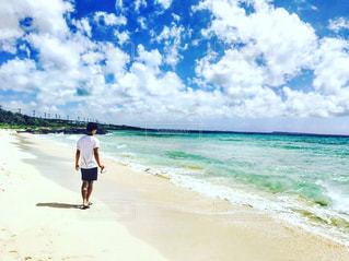 海の隣の浜辺を歩いている男の写真・画像素材[2123975]