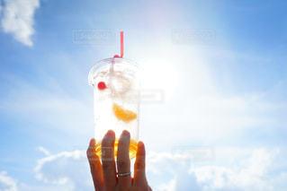 空中にジュースをかざす手の写真・画像素材[2142526]
