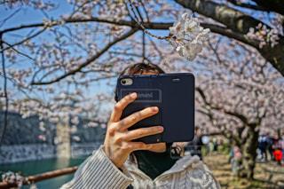 木の前に立っている男の写真・画像素材[2292737]
