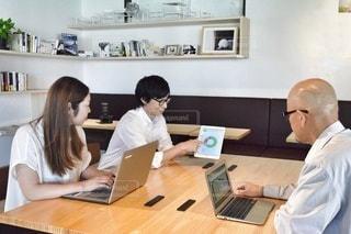 ラップトップコンピュータを使ってテーブルに座っている人々のグループの写真・画像素材[2409753]