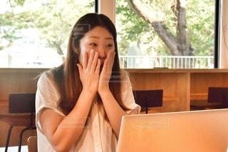 窓の前のテーブルに座っている人の写真・画像素材[2410001]