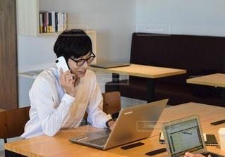 ラップトップコンピュータを使ってテーブルに座っている人の写真・画像素材[2410093]