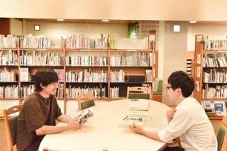 図書館のテーブルに座っている人々のグループの写真・画像素材[2492686]