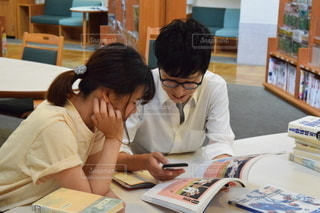 本を見てテーブルに座っている男女の写真・画像素材[2493101]