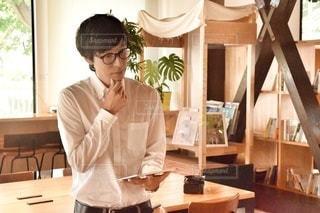 窓の前のテーブルに座っている男の写真・画像素材[2504123]