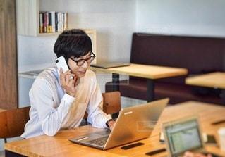 ラップトップコンピュータを使ってテーブルに座っている人の写真・画像素材[2505824]