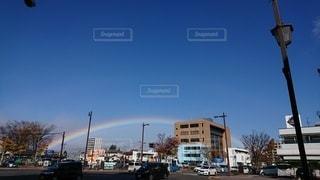 にぎやかな街の通りに現れた虹の写真・画像素材[2507729]