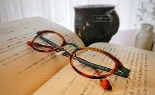 本の上に置いてあるメガネの写真・画像素材[2765899]