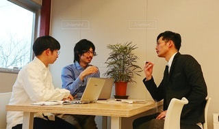 ラップトップコンピュータの前の机に座っている人々のグループの写真・画像素材[2879505]