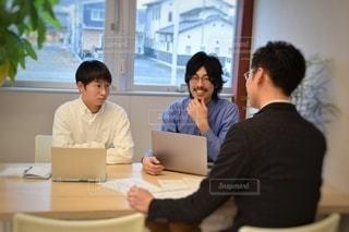 ラップトップを使ってテーブルに座っている人々のグループの写真・画像素材[2880497]