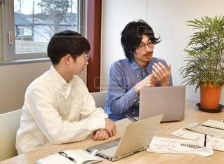 ラップトップコンピュータを使ってテーブルに座っている人々のグループの写真・画像素材[2880698]