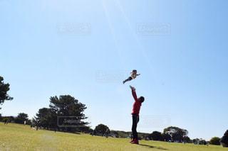 野原で凧を飛ばしている男の写真・画像素材[2189423]