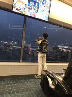 屋内,雨,飛行機,男,背中,後姿,旅行,空港,出発,ターミナル,外は雨,立ち姿