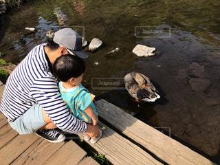 いくつかの水の上に木製のドックに座っている男の写真・画像素材[2184575]