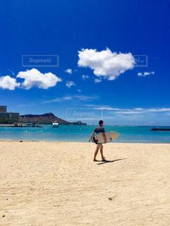 浜辺でサーフボードを持っている男の写真・画像素材[2441158]