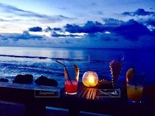 女性,飲み物,自然,風景,海,空,夏,夕日,屋外,夕焼け,夕暮れ,夕方,景色,コップ,人,グラス,夕景