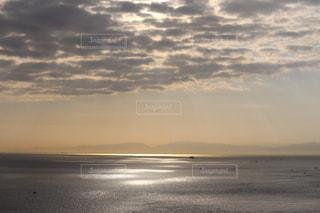 水の上の夕日と雲の写真・画像素材[2429151]