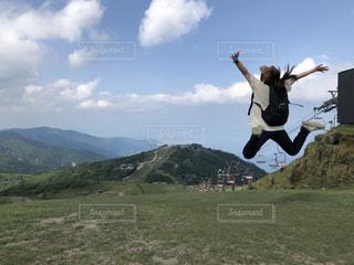 芝生の丘で空中を飛んでいる人の写真・画像素材[2177299]