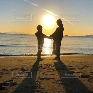 2人,海,空,夕日,太陽,砂浜,夕焼け,夕暮れ,水面,海岸,光,人