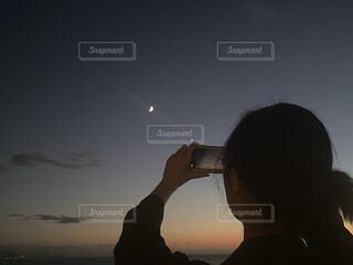 女性,1人,自然,風景,空,夜空,綺麗,後ろ姿,夕暮れ,夕方,景色,女子,スマホ,撮影,見上げる,月,人物,人,三日月,グラデーション,輝き,月の輝き,月フォト
