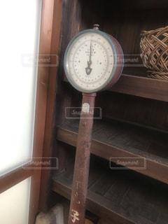 木製のテーブルの上に座っている時計の写真・画像素材[2322722]