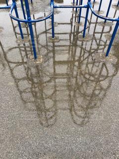フェンスの前に座っている椅子水たまりの写真・画像素材[2216392]