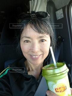 女性,1人,緑,サングラス,黒,車内,ストロー,人,笑顔,グラス,顔,乾杯,美味しい,ドリンク,抹茶ラテ,飲料,シートベルト,ソフトド リンク