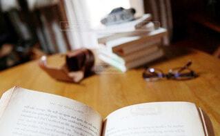 読書とテーブルの上のメガネの写真・画像素材[3772338]