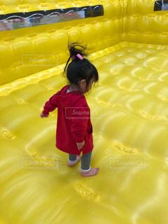 黄色いエアクッションに立つ小さな女の子の写真・画像素材[2386872]
