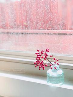 窓の前に花の花瓶が座っているの写真・画像素材[2176465]