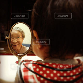 鏡を覗く赤ちゃんと、鏡に映るおばあちゃんの写真・画像素材[2478848]